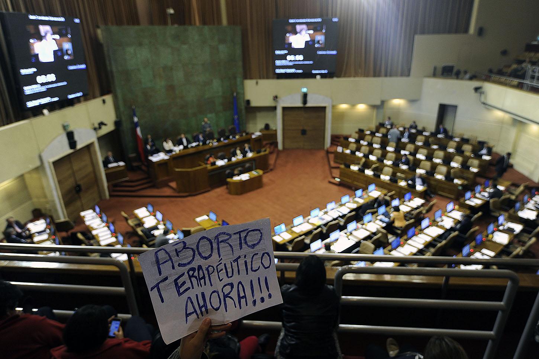 """15 DE MARZO de 2016 /VALPARAISO Una mujer tienen un cartel en las tribunas, durante la discusión del proyecto de ley, en primer trámite constitucional, con urgencia calificada de """"suma"""", que regula la despenalización de la interrupción voluntaria del embarazo en tres causales. PABLO OVALLE ISASMENDI/ AGENCIAUNO"""